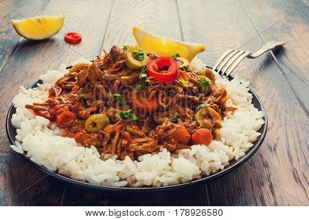 Slow Cooker Ropa Vieja Cuban famously delicious shredded beef stew with pepper and olives on a black plate with a boiled rice and fresh lemon on the wooden table.