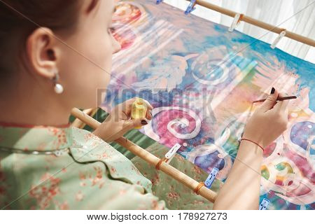 Female artist using liquid yellow color in work