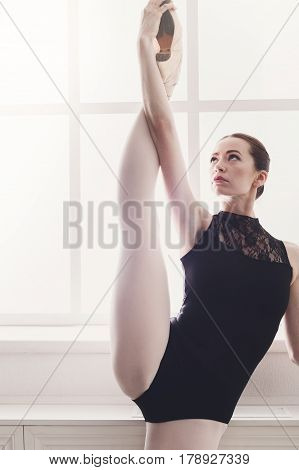 Ballerina shows standing split stretching ballet position at window background. Ballet class training, high-key. Vertical image