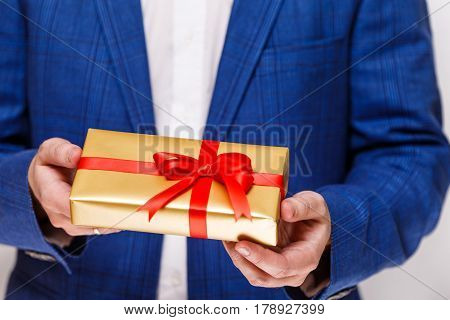 Male hands holding a gift box. Present wrapped with ribbon and bow. Christmas or birthday package. Man in suit and white shirt.