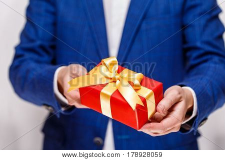 Male hands holding a gift box. Present wrapped with ribbon and bow. Christmas or birthday red package. Man in suit and white shirt.