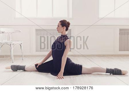 Classical Ballet dancer in split position in class room background. Ballerina training, high-key soft toning.