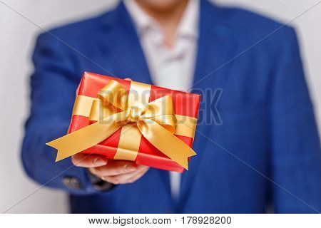 Male hand holding a gift box. Present wrapped with ribbon and bow. Christmas or birthday red package. Man in suit and white shirt.