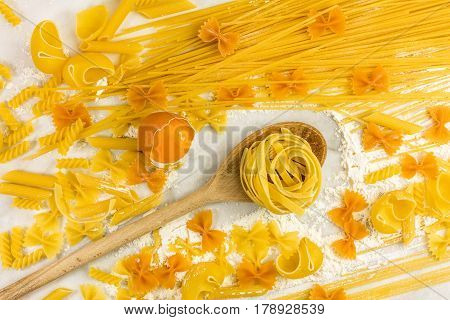Various types of pasta on a white marble table with flour and an egg, shot from above