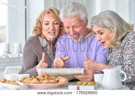 Portrait of three elderly people having breakfast and reading a newspaper