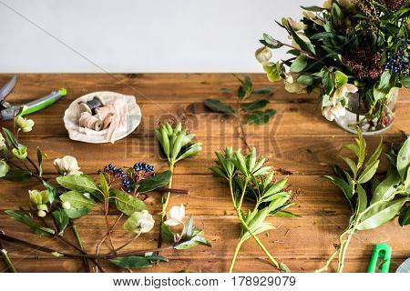 Table of florist. Florist workspace. Scissors, skein harness. Old wooden table. The working surface. Make a bouquet. Hobbies, business occupation