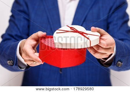 Male hands holding heart-shaped gift box. Opened present wrapped with ribbon and bow. Valentines day love package. Man in suit and white shirt.