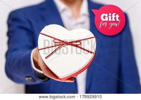 Male hands holding heart-shaped gift box. Present wrapped with ribbon and bow. Gift for you speech bubble. Man in suit and white shirt.