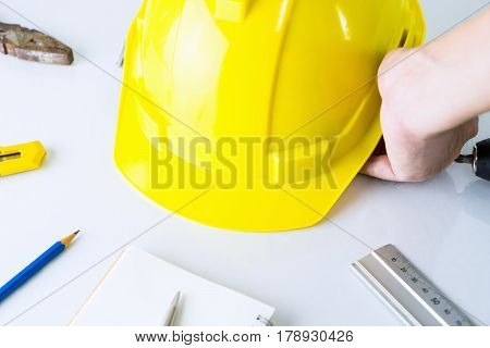 Construction worker is picking up safety helment from tool desk