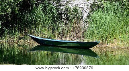 Rowboat moored between the rich coastal vegetation in the lake