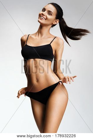 Laughing sexy girl in black bikini posing on grey background. Photo of beautiful girl with slim toned body. Beauty and body care concept