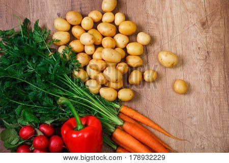 Potatoes with carrot and pepper. Red radish and raw new potato. Fresh natural vegetables. Organic bio food. On wooden table.