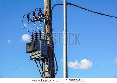 High voltage electrical transformer high on concrete poles .