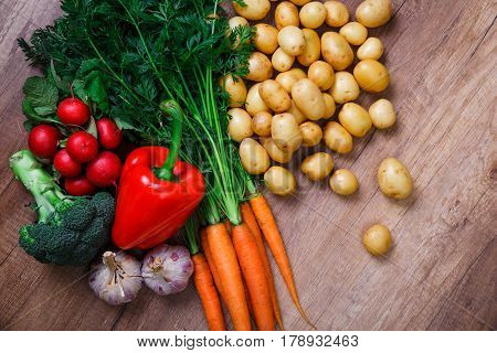 Potatoes with carrot, garlic and pepper. Red radish, brocoli and raw new potato. Fresh natural vegetables. Organic bio food. On wooden table.