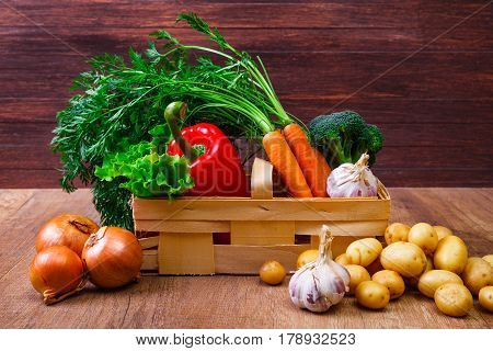 Vegetables. Potatoes, carrot and red pepper. Lettuce salad, garlic and brocoli. Onion. Wooden basket on rustic table.