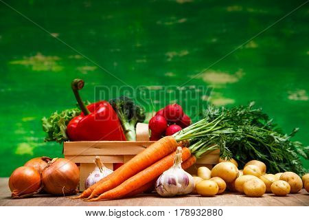 Vegetables. Potatoes, carrot and red pepper. Garlic, onion and brocoli. Lettuce salad and red radish. Wooden basket on green background.