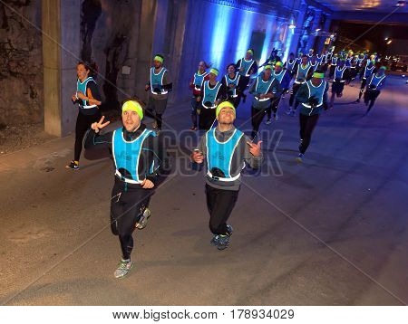 STOCKHOLM SWEDEN - MAR 25 2017: Group of runners from above in blue reflex vest in a tunnel with blue light in the Stockholm Tunnel Run Citybanan 2017. March 25 2017 in Stockholm Sweden
