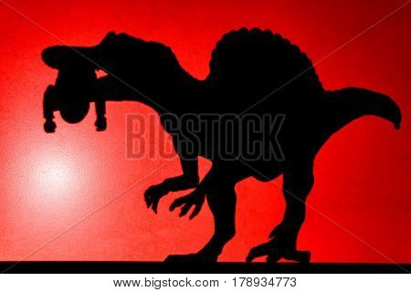 red spot light projection shadow of a spinosaurus with a dead body in its mouth no logo or trademark