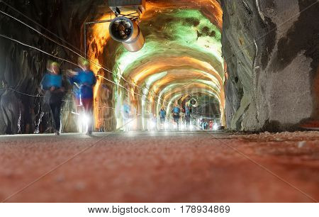 STOCKHOLM SWEDEN - MAR 25 2017: Group of ghost like runners in a tunnel with green and orange light in the Stockholm Tunnel Run Citybanan 2017. March 25 2017 in Stockholm Sweden