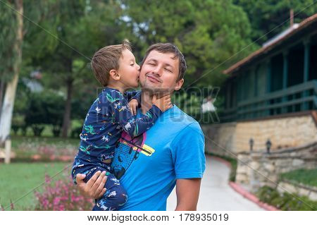 Portrait of a happy father with his little son on vacation. Little boy kisses and hugs his father. Happy fathers day.Happy family. Positive human emotions feelings joy.