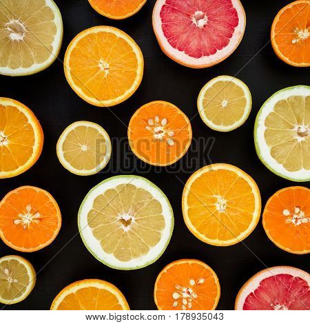 Lemon, orange, mandarin, grapefruit and sweetie on black background. Flat lay, top view. Fruit colorful background