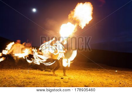 fire show, dancing with flame, male master fakir blowing fire, performance outdoors, flame control man dances with fire, with fire trails on a background draws a fiery figure in the dark, highly in mountains with a moon in a dark blue sky