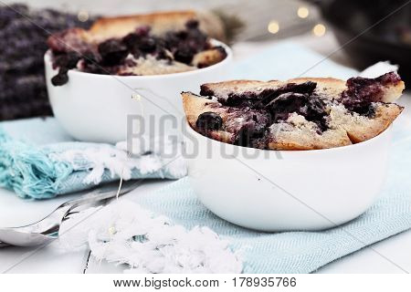 Two bowls of freshly baked homemade blueberry lavender cobbler. Selective focus on dish in foreground with extreme shallow depth of field. Perfect dessert for spring or summer.