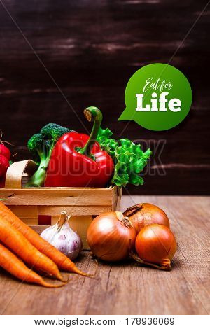 Vegetables. Red pepper, carrot and brocoli. Radish, onion and lettuce salad. Wooden basket on rustic table.