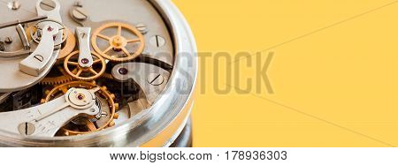 Vintage stopwatch chronometer mechanism macro view, yellow background. Selective focus photo. Copy space photo