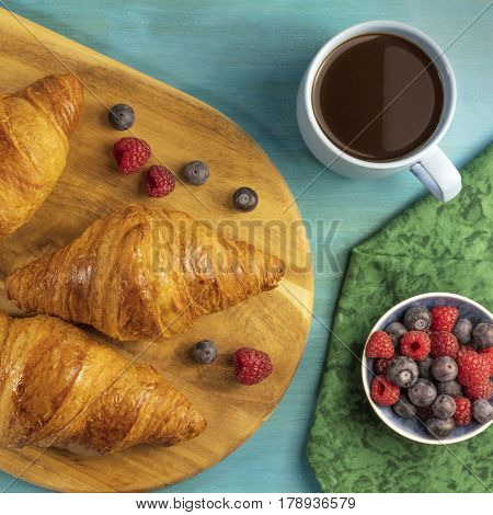 A square photo of crunchy French croissants with fresh raspberries and blueberries on a wooden cutting board with a cup of chocolate