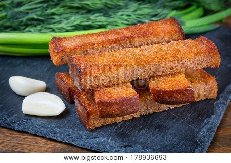 Fried bread croutons toasts on a black stone board