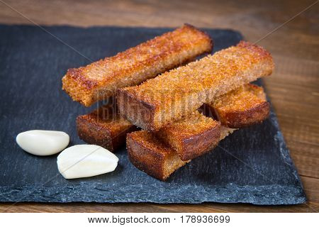 Fried bread croutons toasts and garlic on a black stone board