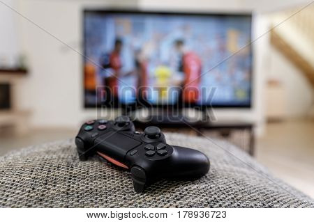 Playing video game. Console controller or joystick. Football or soccer game on the television. Widescreen tv stands on commode.
