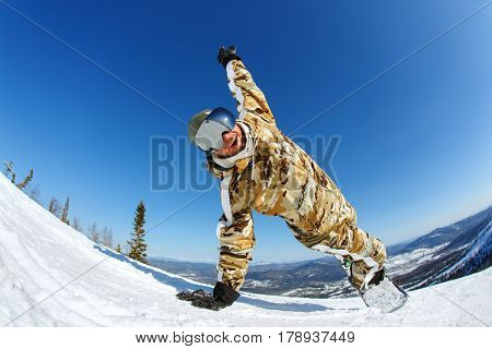A snowboarder with his hands up on the  ski resort of Sheregesh.