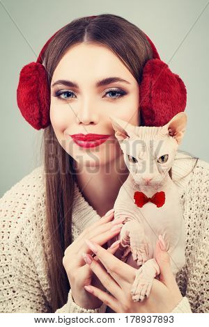 Beautiful Woman Fashion Model in Furry Ear-muffs White Sweater Holding Hairless Cat. Beauty Winter Girl in Knitted Woolen Cloth