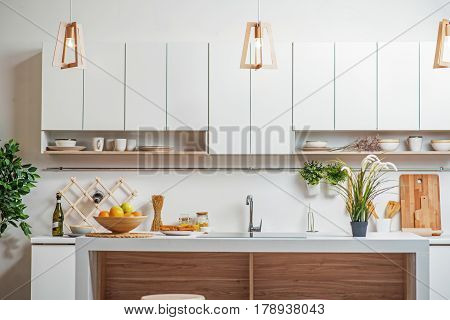 Cozy kitchen with furniture in contemporary style. Wooden chandeliers are hanging under white counter near sink and cupboards. Healthy fruits on board
