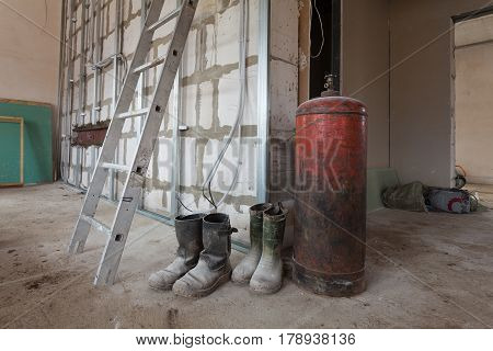 Ladder dusty rubber boots of workers and big gas boiler in apartment during during on the remodeling renovation and construction