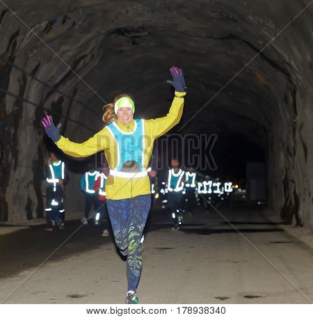 STOCKHOLM SWEDEN - MAR 25 2017: Smiling woman and competitors in reflex vest running in a dark tunnel in the Stockholm Tunnel Run Citybanan 2017. March 25 2017 in Stockholm Sweden