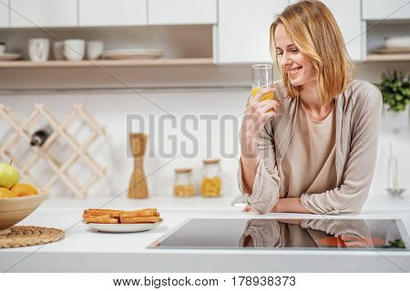Carefree young woman is drinking juice in kitchen. She is standing near electric cooker with relaxation and laughing
