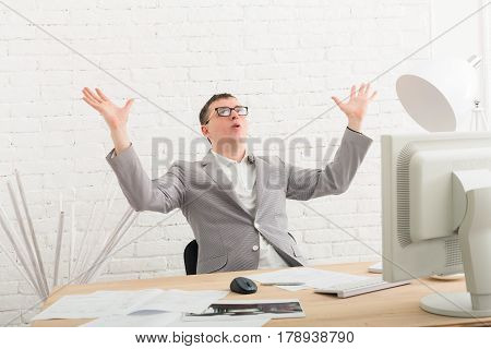 Winner businessman happy, succesful, in white modern office interior, sitting at desk. Office worker in eye glasses, job in internet. High key