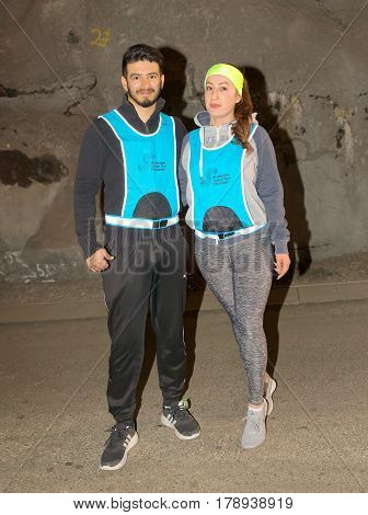 STOCKHOLM SWEDEN - MAR 25 2017: Couple posing during the running race in a dark tunnel in the Stockholm Tunnel Run Citybanan 2017. March 25 2017 in Stockholm Sweden