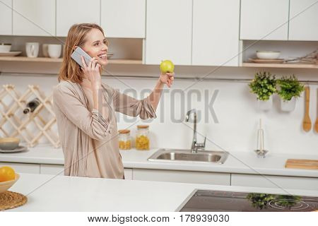 Happy young woman is talking on mobile phone and smiling. She is standing in kitchen and eating apple