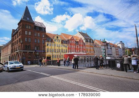 COPENHAGEN DENMARK - JUNE 15: People are walking in Nyhavn a 17th-century waterfront and entertainment district with brightly coloured townhouses bars cafes and restaurants in 2012