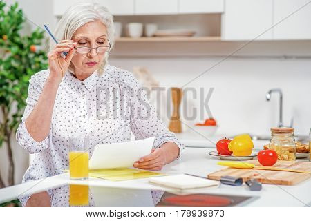 Serious mature housewife is settling financial problems. She is reading paper with concentration while sitting in kitchen