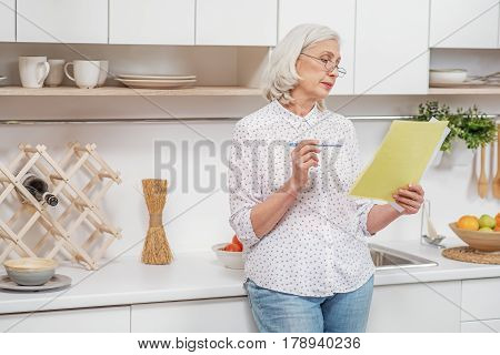 Pensive senior housewife is signing insurance contract. She is standing in domestic kitchen