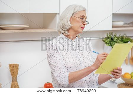 Calm mature woman is signing document with concentration. She is standing at home