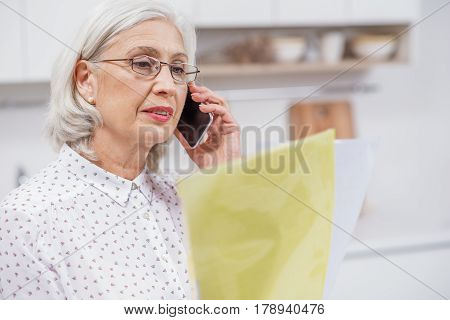 Portrait of confident mature woman speaking with utility service at home. She is reading papers with concentration