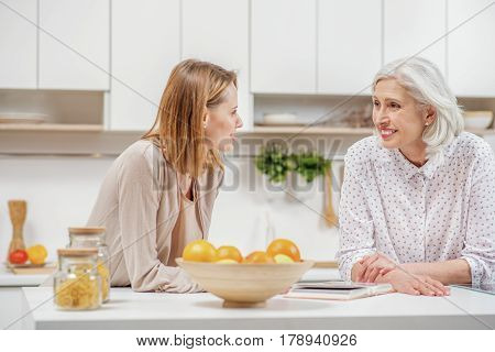 Happy young woman is visiting her old mother. They are standing in kitchen and talking with enjoyment