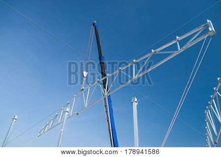 Crane lifting galvanized steel roof truss construction frames with deep blue sky in the background
