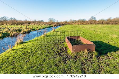 Strange rusty iron trough in a Dutch nature reserve. It's a sunny day in the fall season.